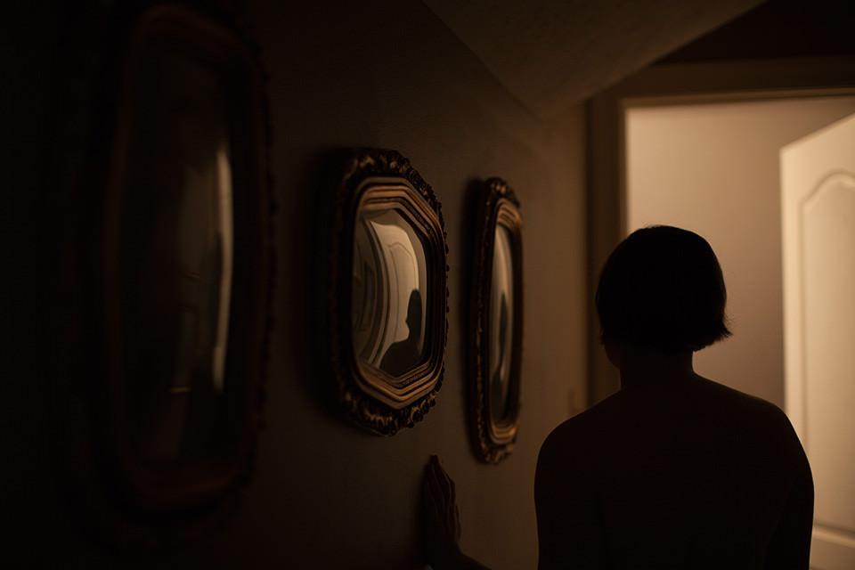 Eine Frau spiegelt sich in den Bilderrahmen im dunklen Flur.