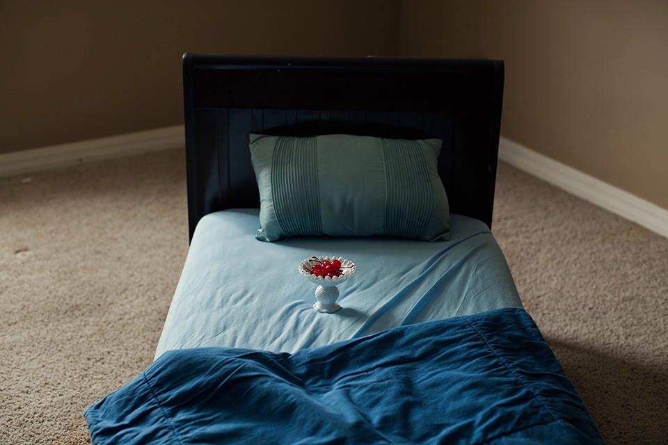 Auf einem Bett steht eine Schale mit Kirschen.