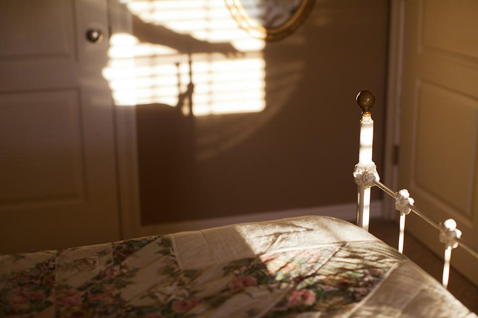 Ein Zimmer mit Bett und Lichtreflexen an der Wand.