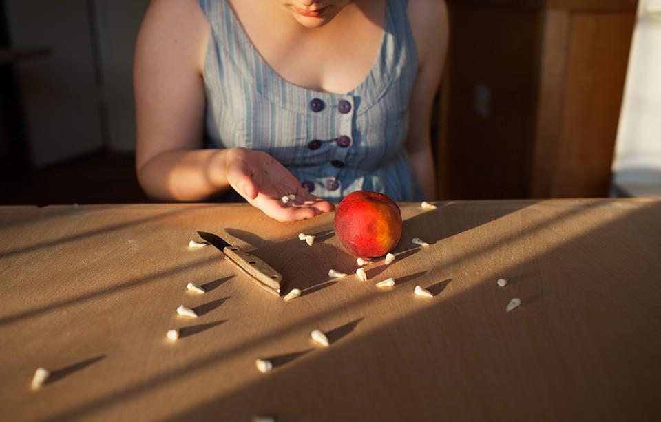 Eine Frau an einem Tisch mit einem Apfel, einem Messer und vielen Zähnen.