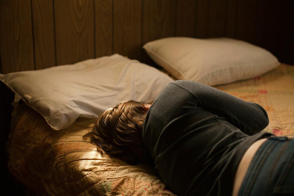 Eine Frau liegt auf einem Bett.