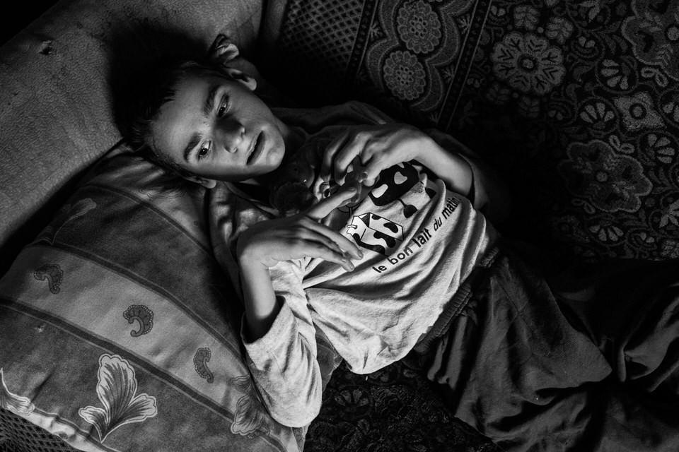 Ein Junge mit Behinderung liegt auf einer Couch und schaut zur Seite.
