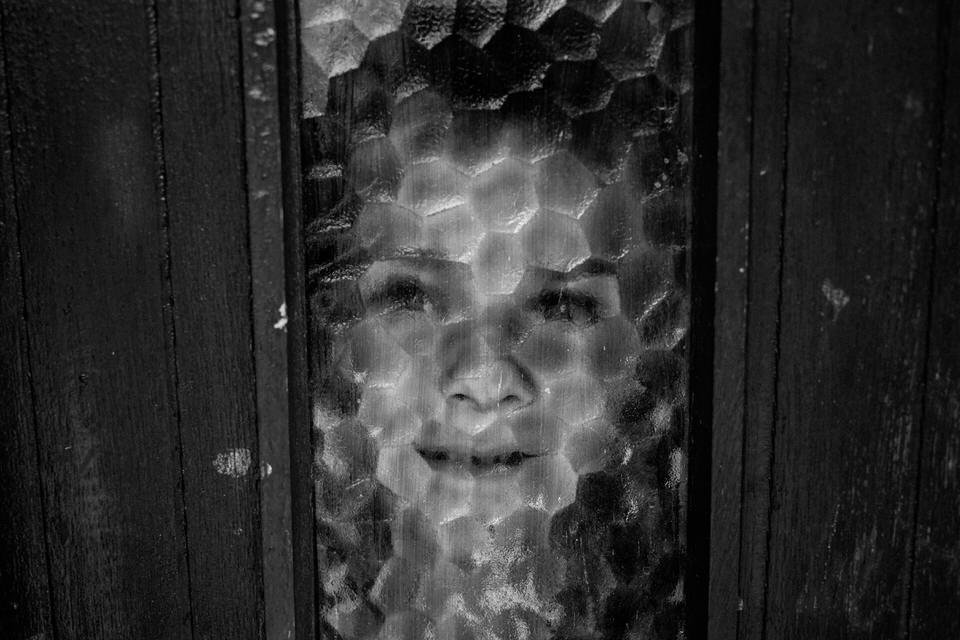 Ein Junge schaut durch das Glas einer Tür.
