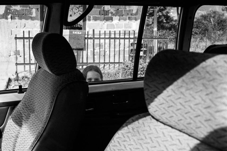 Ein Mädchen versteckt sich hinter einem Auto.