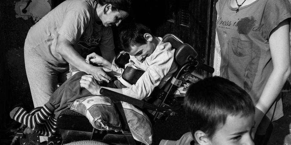 Ein Junge mit Behinderung wird von seiner Mutter in den Rollstuhl gesetzt.