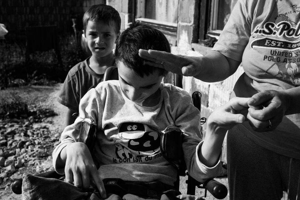 Blick auf den Jungen, seine Mutter hält ihm die Hand vor die Stirn.