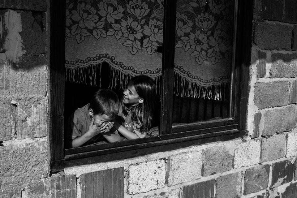 Zwei Geschwister am Fenster.