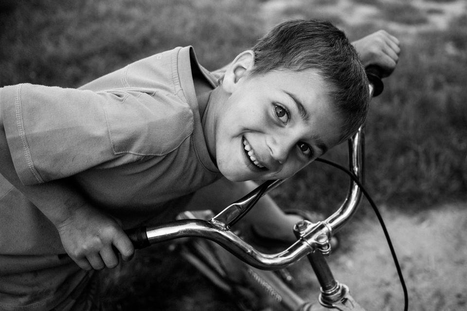 Ein Junge schaut auf seinem Fahrrad in die Kamera.