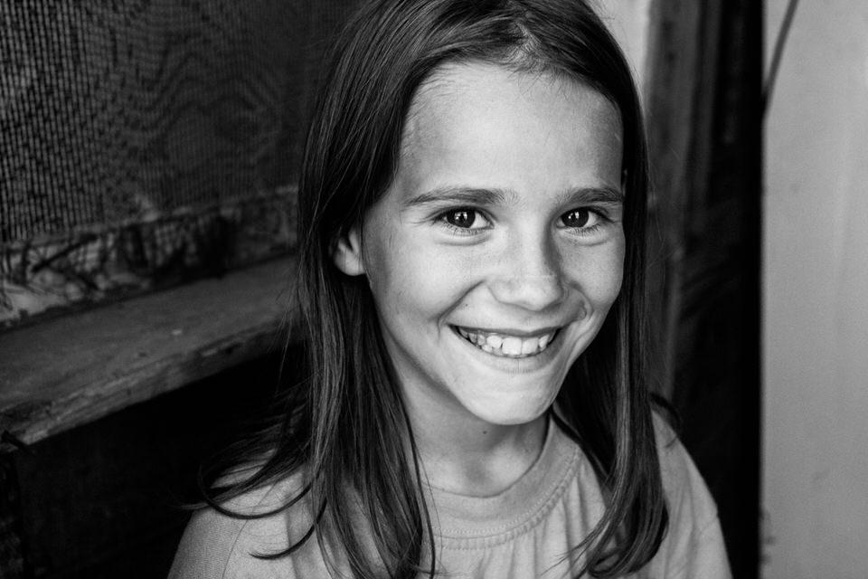 Ein lachendes Mädchen strahlt über das ganze Gesicht.