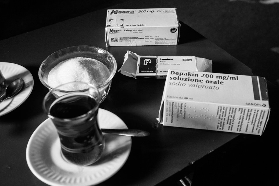 Medikamente neben einem Kaffeeglas.
