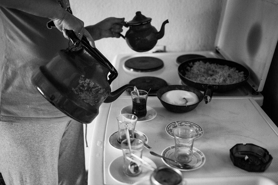 Eine Frau gießt Wasser in kleine Gläser.