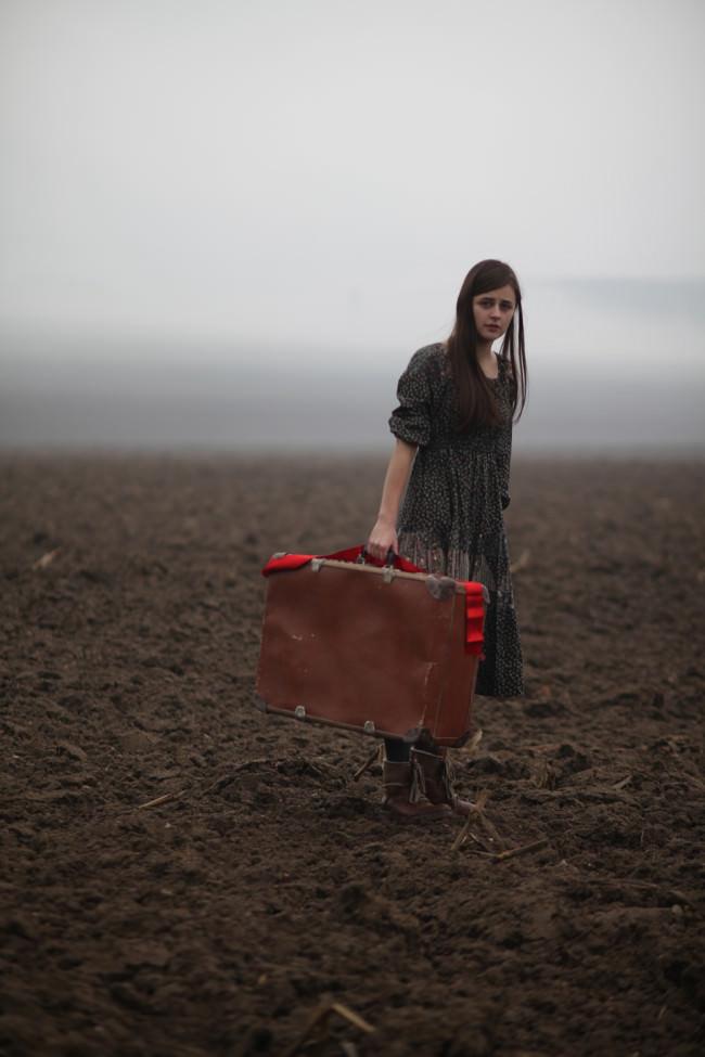 Ein Mädchen steht mit einem Koffer in der Hand auf einem Acker.