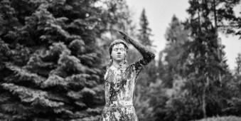 Steinstatue steht in leichtem Schneeregen.