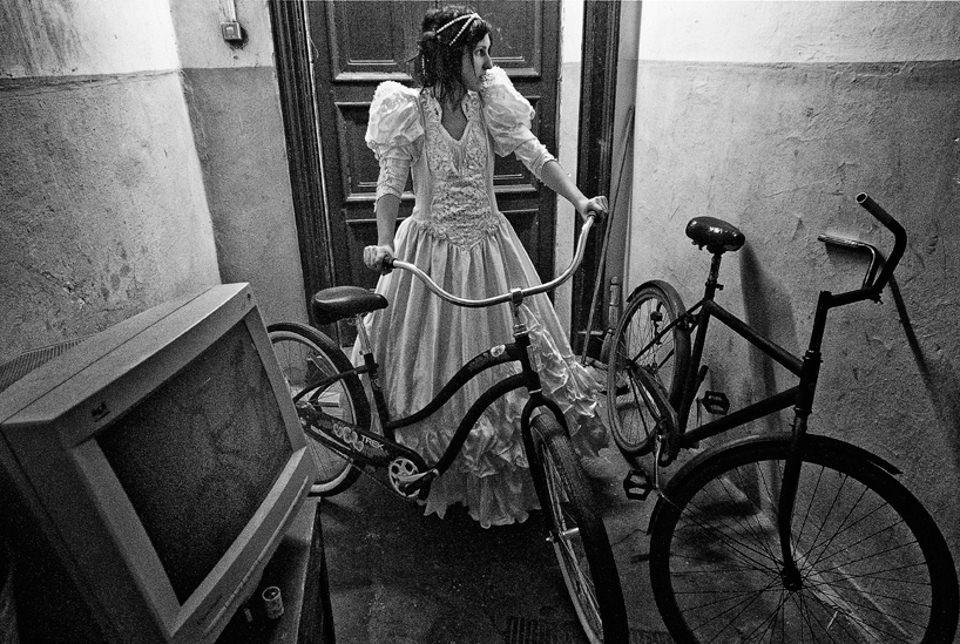 Eine Frau im Bruatkleid steht mit einem Fahrrad im Hausflur.