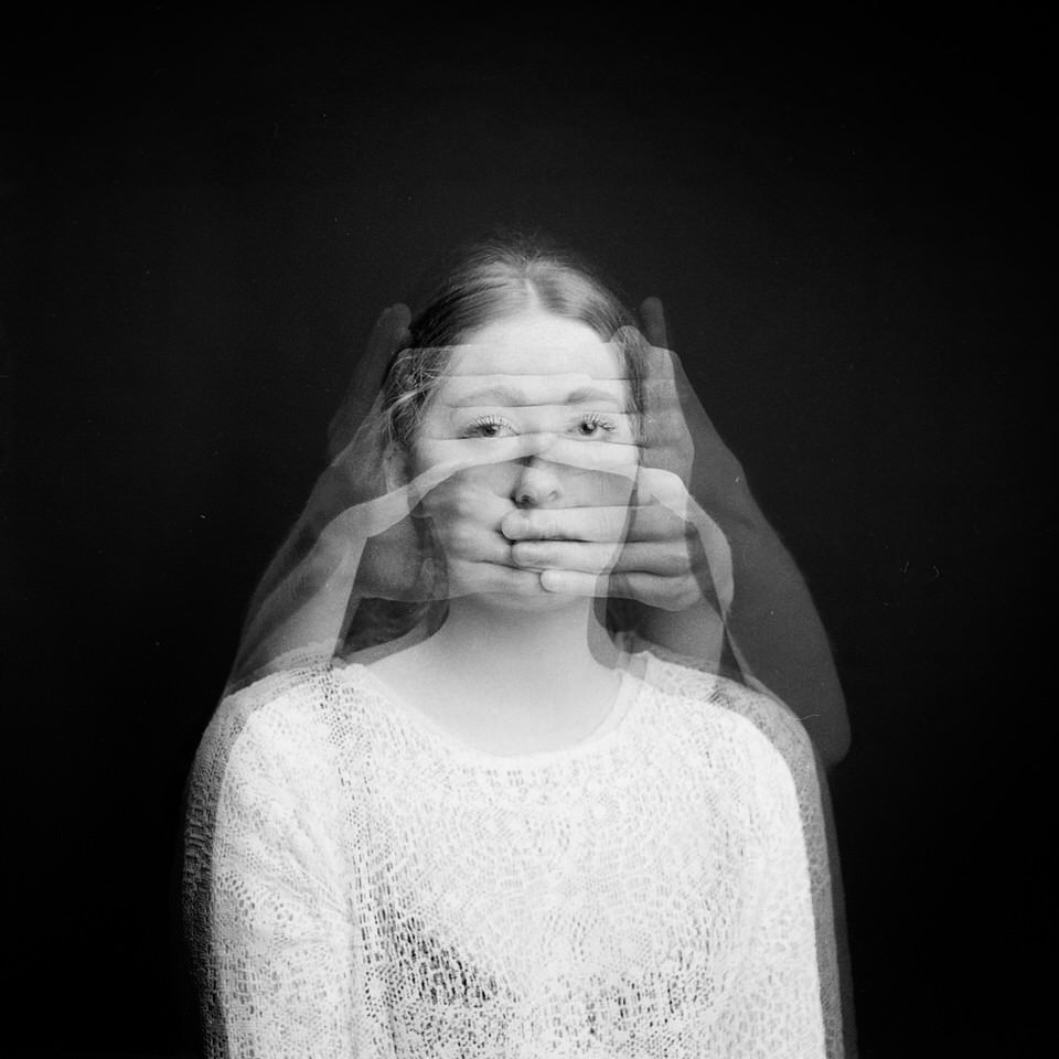 Eine Frau mit Händen vor dem Gesicht. Doppelbelichtung.