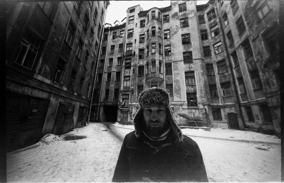 Ein Mann mit Wintermütze steht vor einem verschneiten Gebäude.