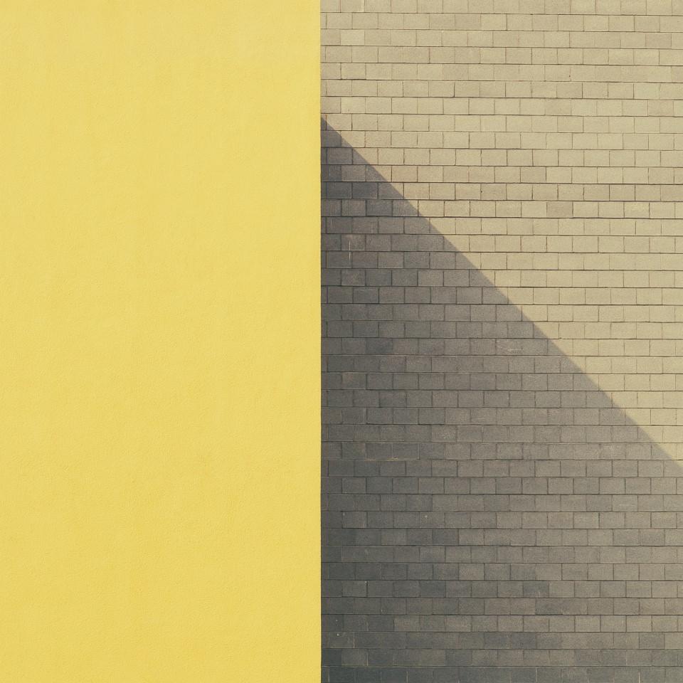 Hauswand, links gelb, rechts hellbraune Ziegel mit diagonalem Schatten.