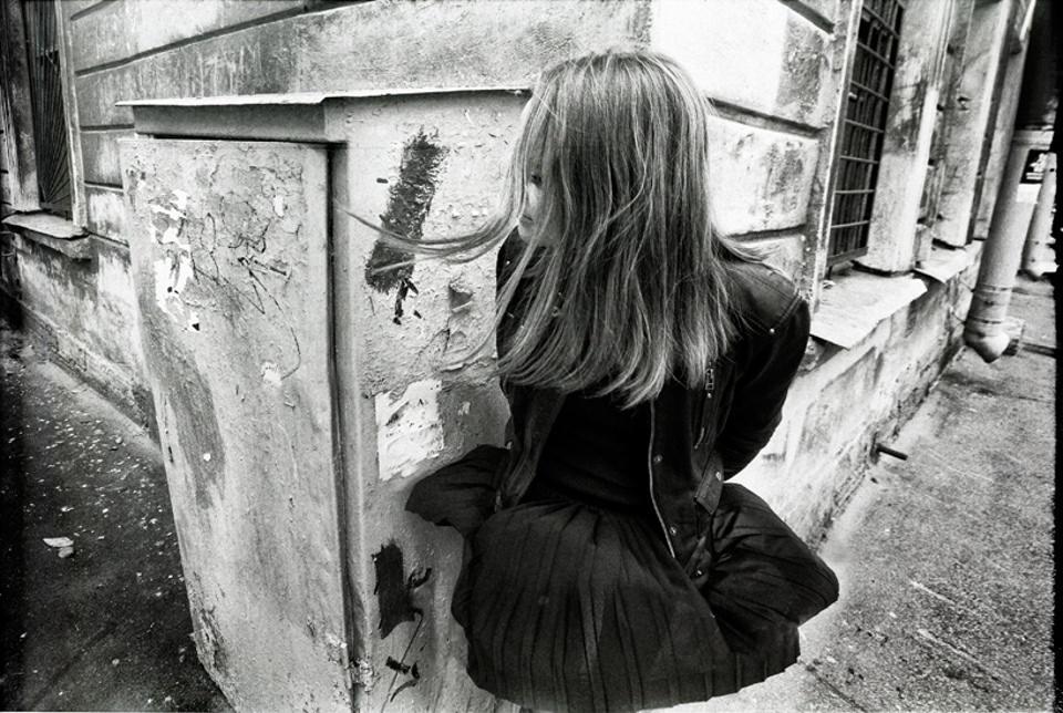 Einer jungen Frau wehen das Kleid und die Haare hoch.