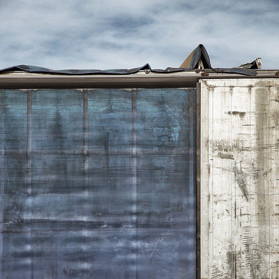 Strukturen und Blauschatierungen an einer Hauswand vor dem Himmel.