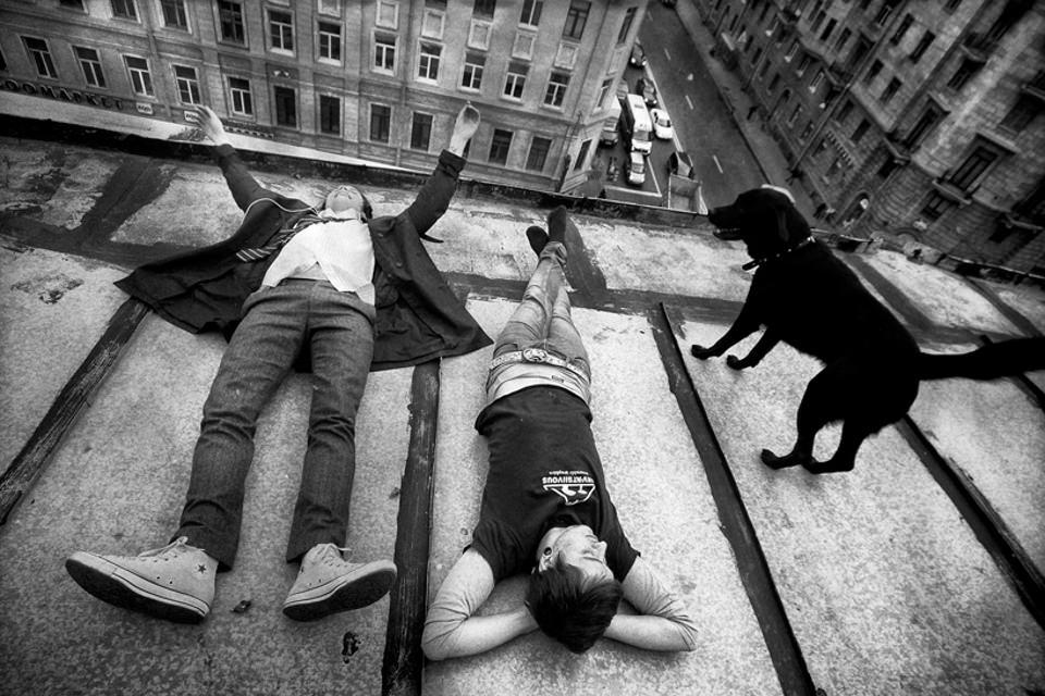 Zwei Männer und ein Hund liegen am Abgrund eines Häuserdaches.