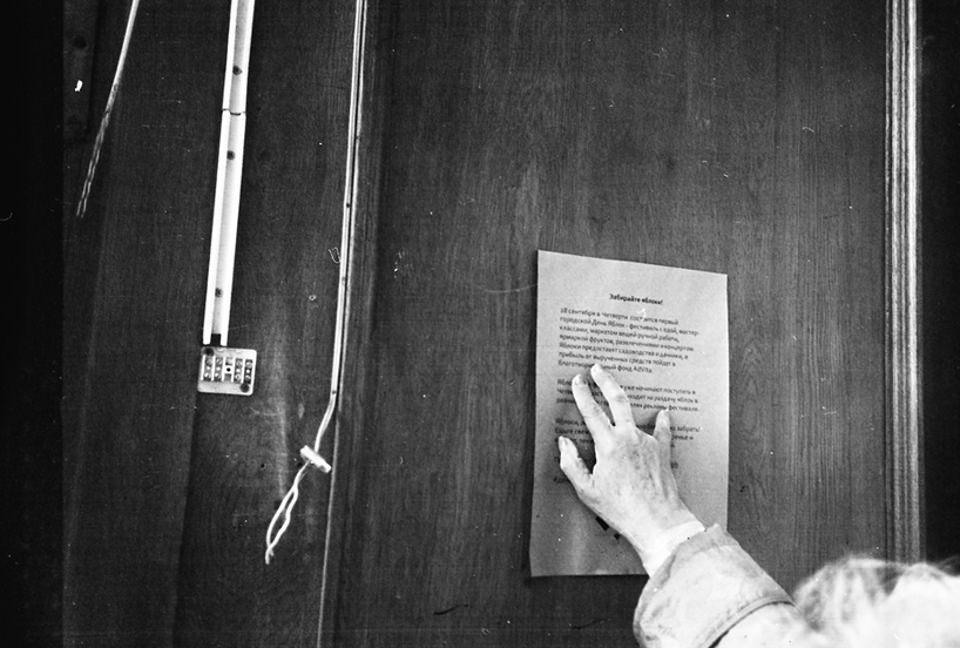 Eine Hand hält ein beschriebenes Papier an eine Wand.