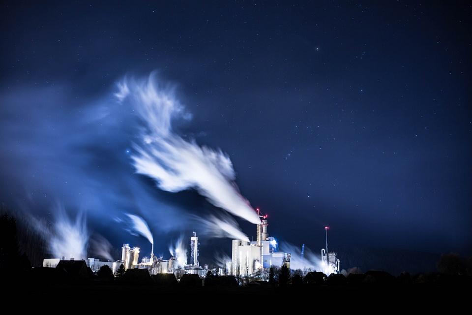 Langzeitbelichtung einer Fabrik mit wehenden Schloten vor dunkelblauem Nachthimmel.