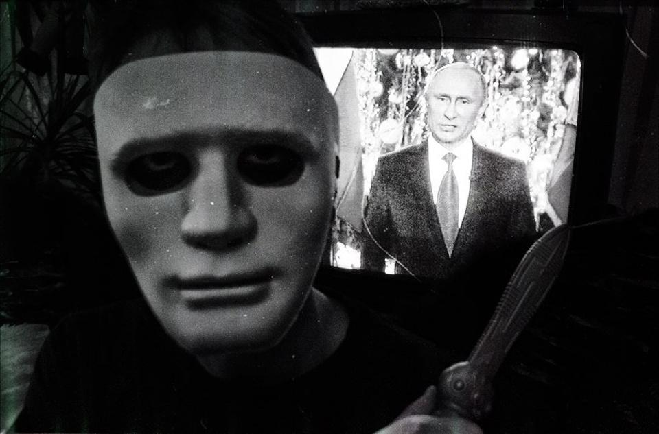 Ein Maskierter steht vor einem Fernseher, auf dem eine Rede von Putin läuft.