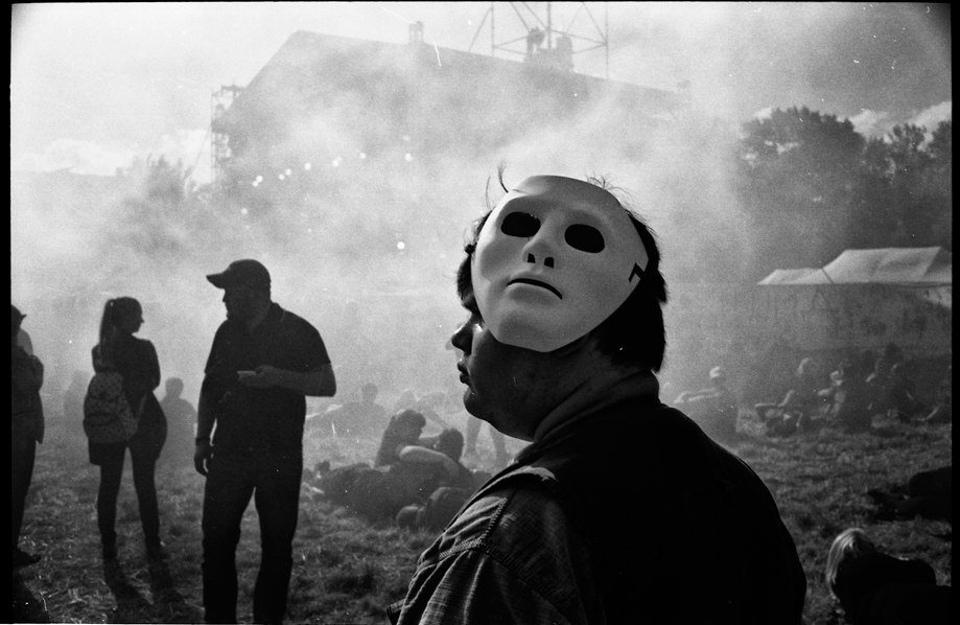 Ein Mann mit einer weißen Maske steht im Rauch.