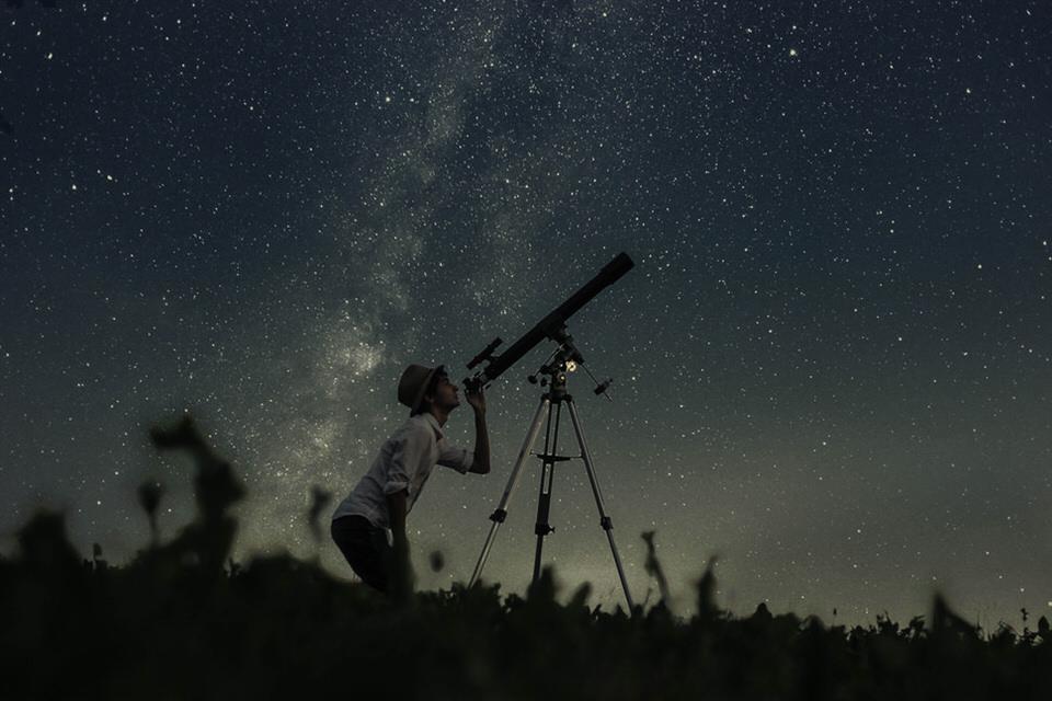 Ein Mann mit Teleskop beobachtet den Sternenhimmel.