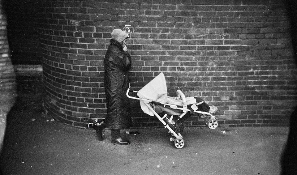 Eine Frau in dickem Mantel raucht und schiebt einen Kinderwagen vor sich her.