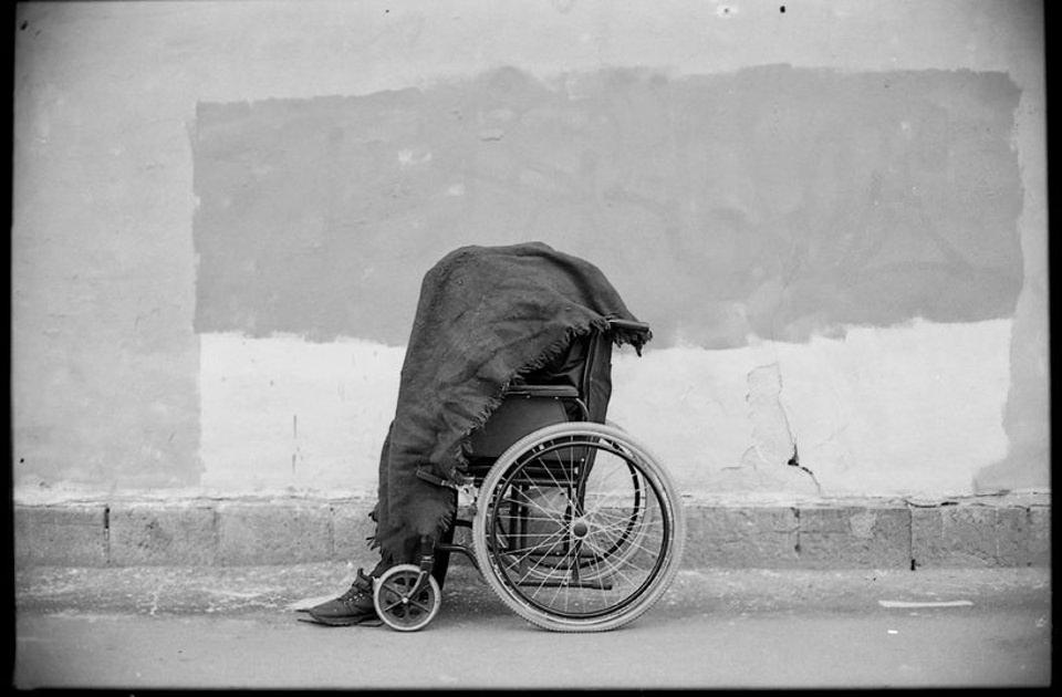 Eine Person in einem Rollstuhl ist von einer Decke bedeckt.