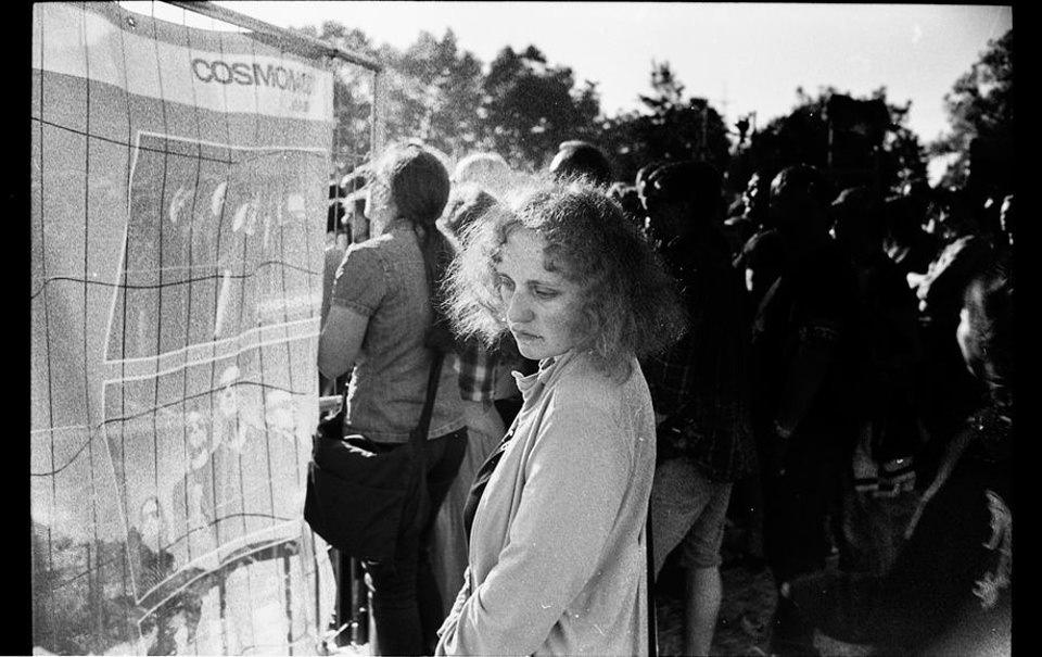 Eine Frau steht abseits von einer Menge und schaut vor sich hin.