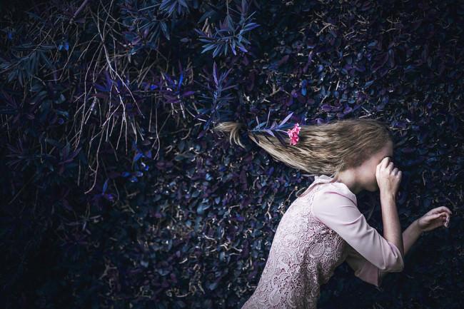 Eine Frau vor einem Busch hält sich die Augen zu.