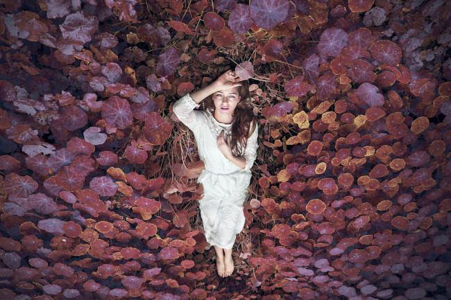 Eine Frau liegt in roten Blättern.
