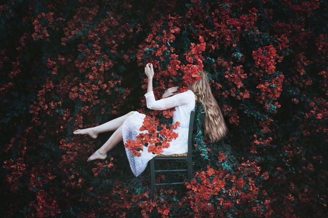 Eine Frau sitzt auf einem Stuhl inmitten eines Busches.
