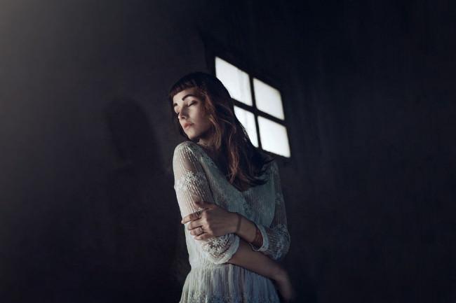 Eine Frau steht in einem dunklen Zimmer, hinter ihr ein kleines Fenster.