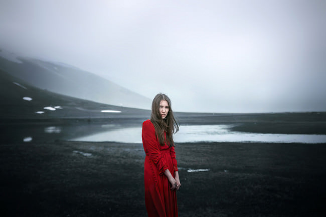 Eine Frau in rotem Kleid steht in eisiger Landschaft.