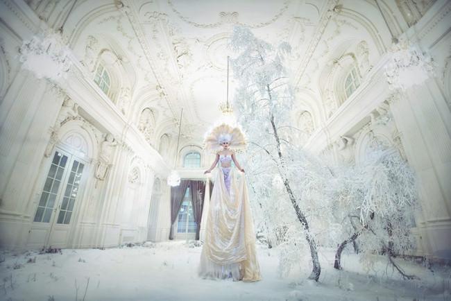 Eine Frau in weißem Kleid steht in einem Raum voller Schee.