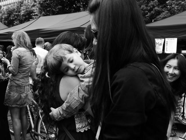 Ein Kind träumt auf dem Arm einer Mutter.