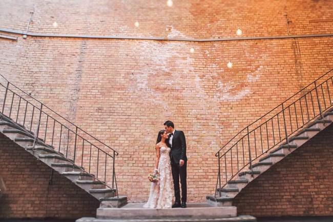 Ein Brautpaar vor einer Ziegelwand.