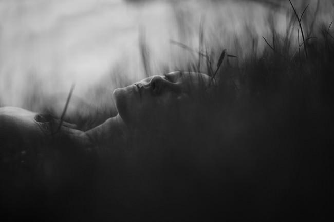 Eine Frau schläft im Gras.