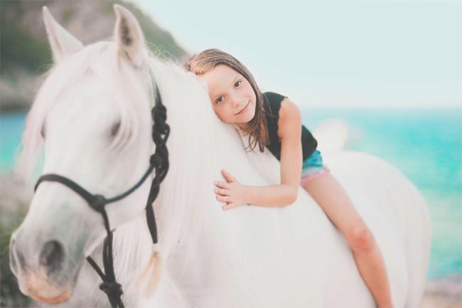 Ein Mädchen auf einem weißen Pferd.