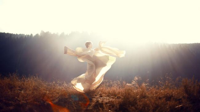 Eine Frau in weißen fliegenden Tüchern im Gegenlicht.