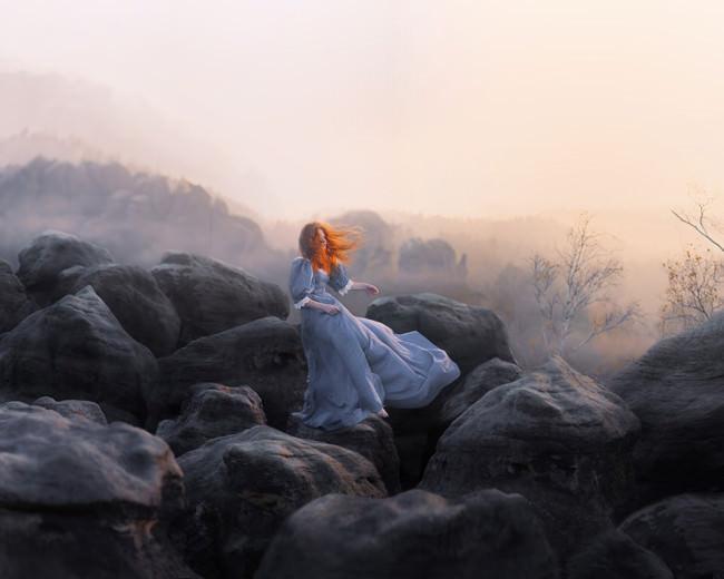 Eine Frau in blauem Kleid in steiniger Landschaft.