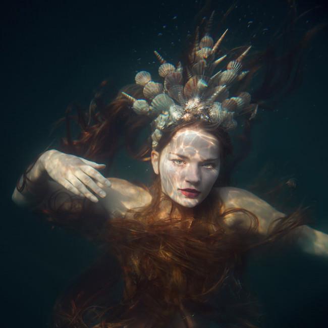 Eine Meerjungfrau mit Muschelkrone Unterwasser.
