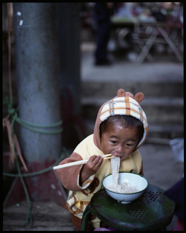 Ein kleines Kind  mit Bärenkapuze isst Nudeln.