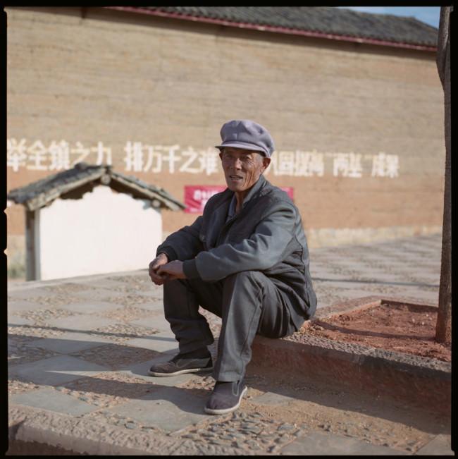 Ein älterer Mann sitzt am Gehweg und schaut in die Kamera