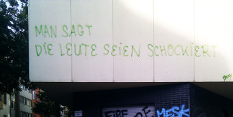 Blick auf eine Wand, auf der steht: Man sagt, die Leute seien schockiert.