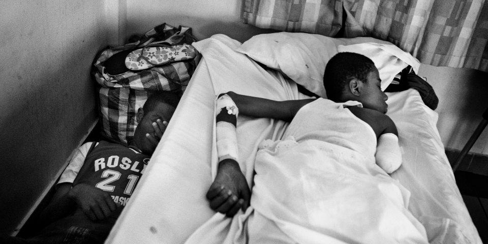 Ein Kind, das einen Arm verloren hat, liegt auf einem Bett,