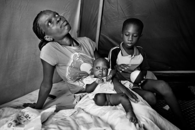 Eine Mutter mit ihren Kindern, von denen das jüngere kein Bein mehr hat.